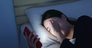 Woman feeling eye pain and lying on bed at night