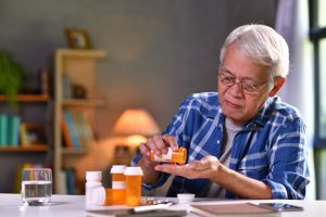 Asian senior man taking medicine at home