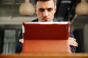 Confident businessman sitting with tablet computer