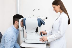 Optometrist checking patients vision at modern clinic
