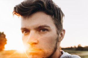 stylish hipster man looking in sunlight in summer evening field