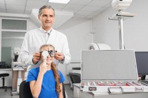 Professional ophthalmologist checking eyesight of girl.