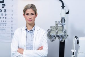 Portrait of beautiful female optometrist standing with arms crossed in ophthalmology clinic