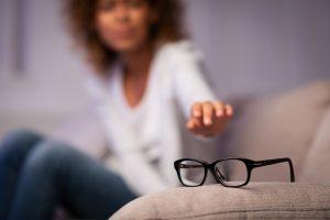 Eyesight problem. Woman reaching for eyeglasses on sofa