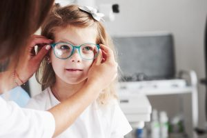 New look. Doctor giving the child new glasses for her vision.