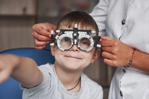 Kid smiling and raising hand while undergoing eye test with phoropter
