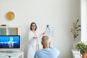 Wide angle portrait of young female ophthalmologist pointing at eye chart while testing eyesight of senior patient, copy space
